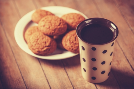 Cup of coffee and cookie. Photo in old color image style. photo