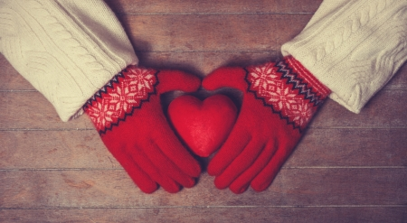 Hands in mittens holdin heart toy. Photo in old color imagestyle. photo
