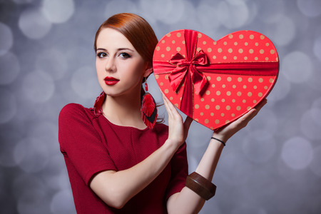 Redhead girl with shape heart box. Photo red background with bokeh. photo