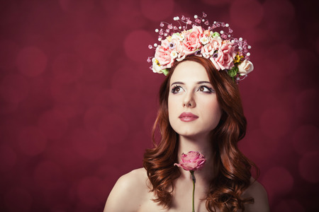 Beautiful redhead women with wreath on red backgrund. photo