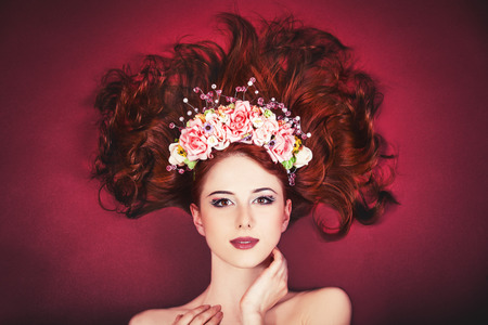 Beautiful redhead women with wreath on red backgrund. Background has stylized roughness. photo