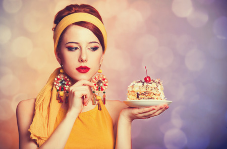 50s fashion: Style redhead girl with cake. Photo with bokeh at background.