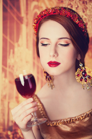 Portrait of the beautiful redhead women with wine. photo