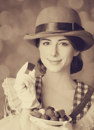 sweettooth: Beautiful women with candy. Photo in retro style with bokeh at background.