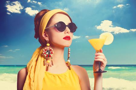 カクテルを片手に浜辺のかわいい赤毛の女性。 写真素材