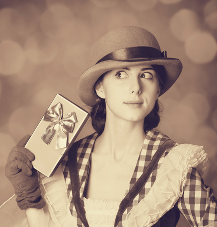 Beautiful women with gift. Photo in retro style with bokeh at background. photo