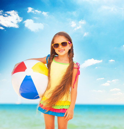 Little girl playing on beach with ball. photo