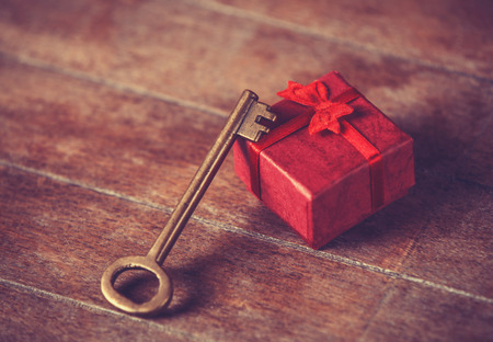 Retro key and little red gift on wooden table. photo