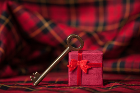 Retro key and little red gift on a tablecloth. photo