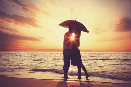love kiss: Couple kissing under umbrella at the beach in sunset.