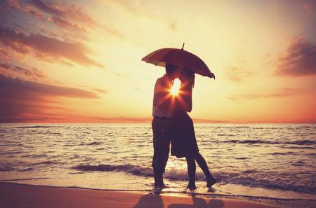 novios besandose: Pareja bes�ndose bajo el paraguas en la playa en el atardecer.