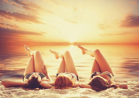 Three girls on the beach in sunset. photo