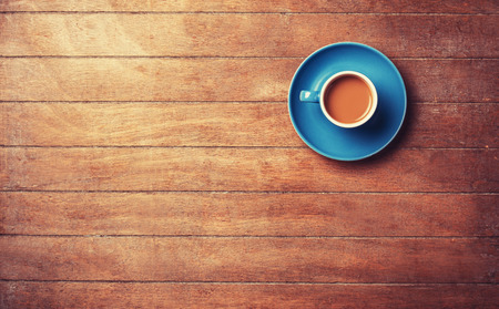 table: Cup of offee on a wooden table.