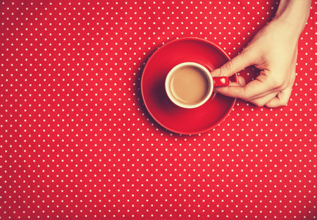Female hand holding cup of coffee. Banco de Imagens
