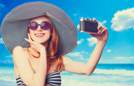 taking video: Beautiful redhead woman making selfie on a beach.