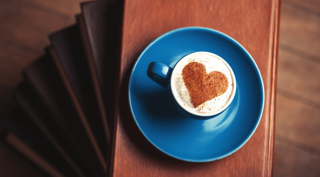 Cup of сoffee with shape heart and book on a wooden table. photo