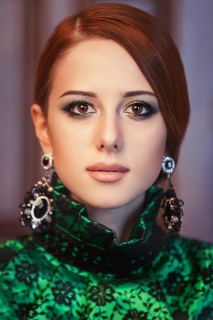 Portrait of a beautiful redhead women with earrings. photo