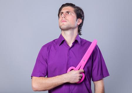 Mann mit großen Schere auf grauem Hintergrund.