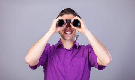 Handsome man with binocular on gray background. photo