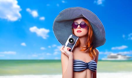 Redhead girl with retro camera on the beach  photo