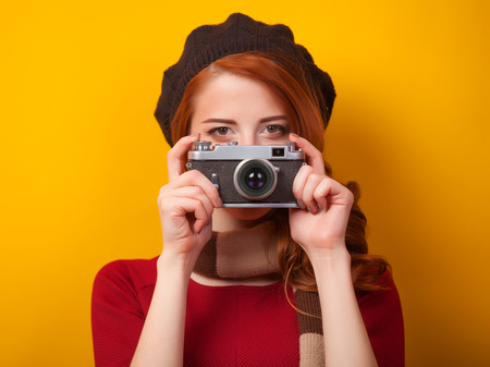 Redhead women with scarf and vintage camera on yellow background. photo