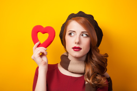 Redhead girl with shape heart on yellow background. photo
