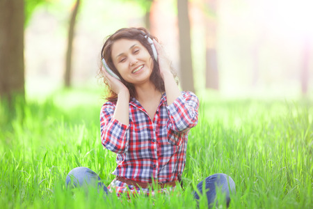 indian summer: Indian girl with headphones in the park.