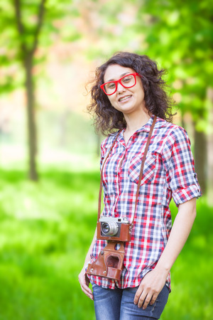indian summer: Indian girl with camera in the park. Stock Photo