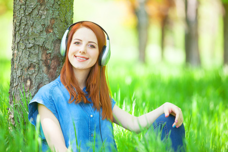 Redhead women with headphones in the park. photo