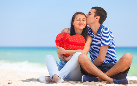 couple cuddling: Young couple with gift on the beach in summer day.