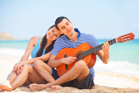 boy playing guitar: Young couple with guitar on the beach in summer day. Stock Photo