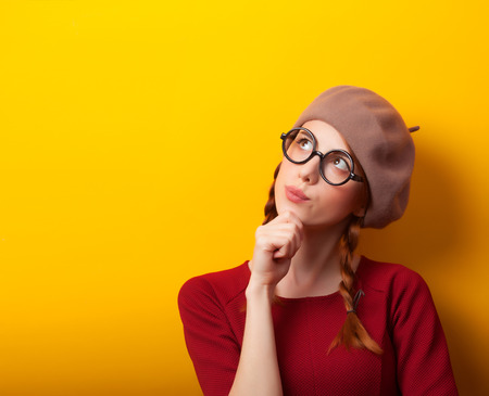 Redhead girl with pigtails on yellow background. Stock Photo