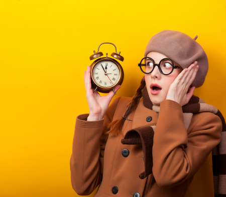 Redhead girl with alarm clock on yellow background. photo