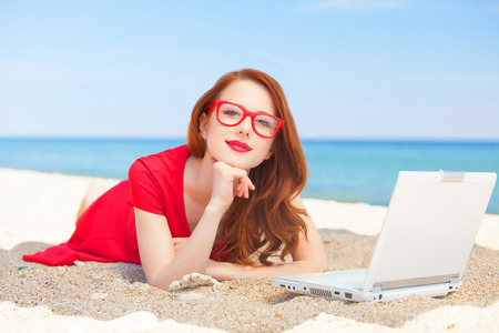 Redhead girl in the glasses with notebook on the beach photo