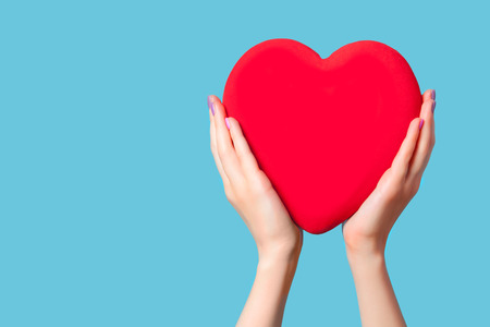 Hands holding shape heart on blue background. Stock Photo