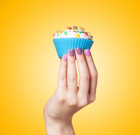 vanilla cupcake: Hand holding cupcake on yellow background Stock Photo
