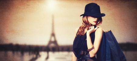 파리 배경에 쇼핑 가방과 함께 빨간 머리 여성.