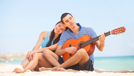 Young couple with guitar on the beach in summer day. photo