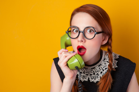 cool girl: Redhead girl with green phone on yellow background.