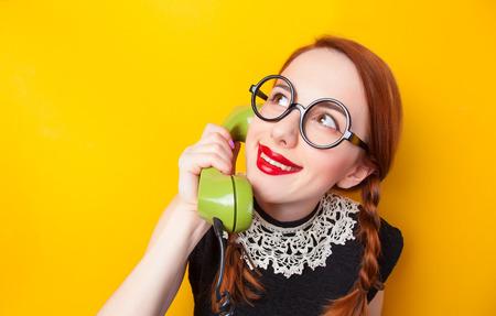 wow: Chica pelirroja con el tel�fono verde sobre fondo amarillo.
