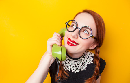 Redhead girl with green phone on yellow background. photo