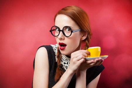 Redhead girl with cup of coffee on red background. photo