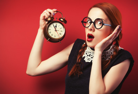 Surprised redhead girl with clock. photo