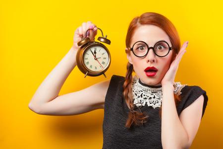 Surprised redhead girl with clock. Reklamní fotografie