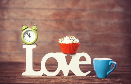 Cupcake, coffee, alarm clock and word Love on wooden table. photo