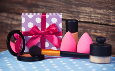 aureate: Cosmetics and gift box on woodent table.