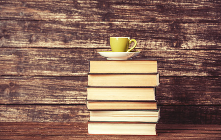 Books and cup of coffee on wooden background. photo