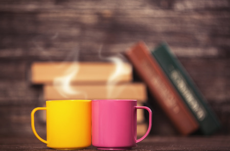 Two cups and books on background. photo