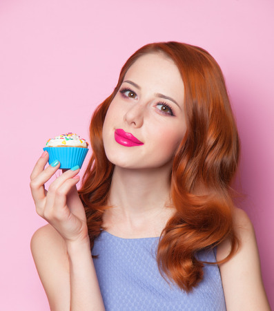 Redhead girl with cupcake in pink background. photo