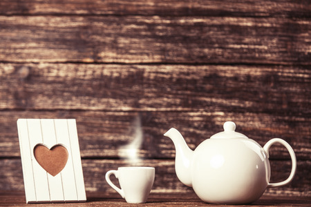 teakettle: Teapot and cup of coffee with frame on wooden table. Stock Photo